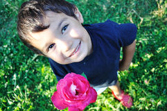 Happy beautiful child on ground with rose outdoor Stock Image