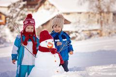 Happy beautiful children, brothers, building snowman in garden Royalty Free Stock Photography