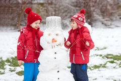 Happy beautiful children, brothers, building snowman in garden Royalty Free Stock Photos