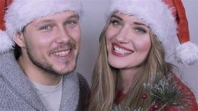 Happy beautiful Christmas couple singing carols in studio. Slow motion. stock video footage