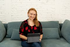Happy beautiful confident freelance woman working at home with tablet on her online new company. Portrait of a successful entrepreneur woman working on digital stock photo