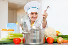 Happy  cook  in toque prepares vegetarian lunch Royalty Free Stock Photography