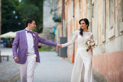 Happy beautiful couple, bride and groom holding hands in a stree Stock Images