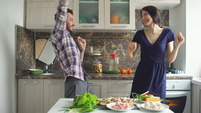 Happy beautiful couple dancing rocknroll while cook on the kitchen at home