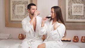 Happy beautiful couple drinking champagne and laughing in spa center. Happy beautiful couple drinking champagne and laughing in spa center stock video footage