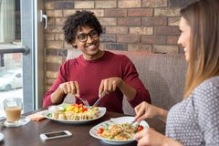 Happy beautiful couple having lunch at a restaurant. While smiling royalty free stock photo