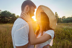 Happy beautiful couple hugs in park in the on the sunset. Stock Image