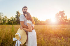 Happy beautiful couple hugs in park in the on the sunset. Royalty Free Stock Image