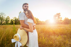 Happy beautiful couple hugs in park in the on the sunset. Stock Photography