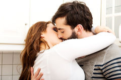 Happy beautiful couple kissing in the kitchen. Stock Images