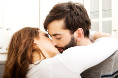 Happy beautiful couple kissing in the kitchen. Royalty Free Stock Photography
