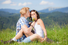 Happy beautiful couple in love. On the green grass field Stock Photography