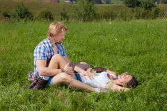 Happy beautiful couple in love. On the green grass field stock image