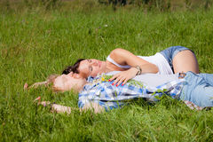 Happy beautiful couple in love. Lying on the green grass meadow stock photography