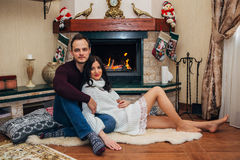 Happy beautiful couple in love near fireplace posing at the camera Stock Photography