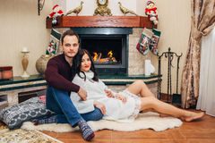 Happy beautiful couple in love near fireplace posing at the camera Stock Images