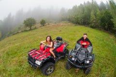 Happy beautiful couple sitting on four-wheelers ATV Stock Photo