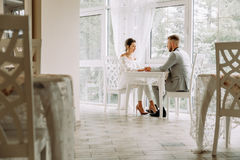 Happy beautiful couple sitting in a restaurant and talking Stock Image