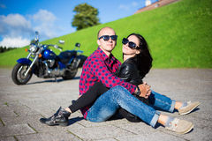 Happy beautiful couple sitting on the road with retro motorbike Royalty Free Stock Photography