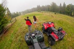Happy beautiful couple standing near four-wheelers ATV Stock Image
