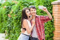 Happy beautiful couple taking a selfie on a mobile phone. huging and have a fun together.  stock photo
