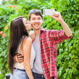 Happy beautiful couple taking a selfie on a mobile phone. huging and have a fun together.  royalty free stock photo
