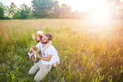 Happy beautiful couple with their Alabai dog in nature with sunset. Royalty Free Stock Photo