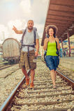 Happy and beautiful couple of tourists walking on the tracks at Royalty Free Stock Photos