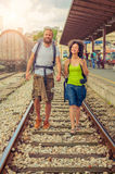 Happy and beautiful couple of tourists walking on the tracks at Royalty Free Stock Photography