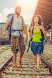 Happy and beautiful couple of tourists walking on the tracks at Stock Photo