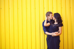 Happy beautiful couple on a yellow wall Royalty Free Stock Photos