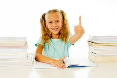 Happy beautiful cute with blond hair little schoolgirl likes studying and reading books in creative education concept with Back to royalty free stock photo