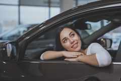 Lovely young woman buying new car at the dealership royalty free stock images