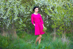 Happy beautiful dreamy woman in pink dress in spring cherry gard Stock Image