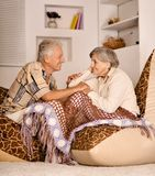 Portrait of happy beautiful elderly couple resting on sofa at home royalty free stock image