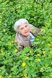 Happy beautiful elderly woman sitting on a glade Royalty Free Stock Photos