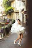 Happy beautiful emotional sexy brunette bride showing legs in fr Royalty Free Stock Image