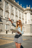 Happy beautiful exchange student girl visiting Madrid city reading map Royalty Free Stock Photography
