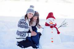 Happy beautiful family building snowman in garden, winter, mom a. Happy beautiful family building snowman in garden, winter time, mom and kid Stock Photos