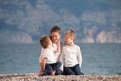 Happy beautiful family consisting of smiling mother and two kids sitting on sea beach in cool summer sunset day Stock Photography