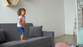 Happy beautiful family daughter laughing  stand on the couch, monkeying and fool around. Child having fun enjoy connection and warm relationships, portrait stock footage