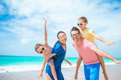 Family beach vacation. Happy beautiful family of four on white beach Stock Images
