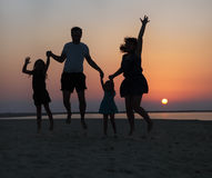 Happy beautiful family jumping on the beach at the sunset Stock Photos