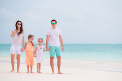 Happy beautiful family with kids walking together on tropical beach during summer vacation Stock Photography