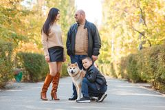 Happy beautiful family walking with dog in the park. Animal concept. Beautiful happy people having fun with doggie in the park outdoors. Happy family with puppy Royalty Free Stock Photography