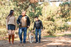 Happy beautiful family walking with dog in the park. Animal concept. Beautiful happy people having fun with doggie in the park outdoors. Happy family with puppy Stock Photo