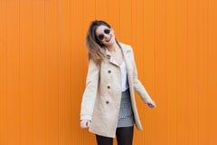 Happy beautiful fashion young woman dancing smiling over orange Stock Photo
