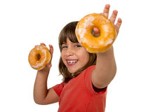Happy beautiful female child having fun playing with two sugar donuts smiling excited Royalty Free Stock Photography