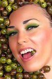 Happy beautiful female face in the gooseberry Stock Photography