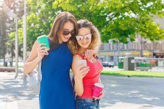 Happy female friends with smartphone outdoors Royalty Free Stock Photos